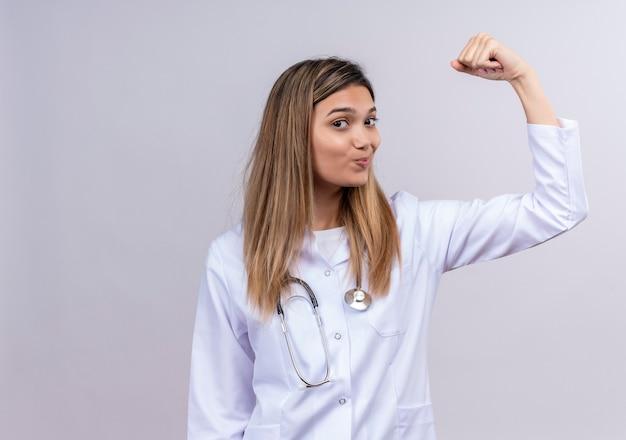 自信を持って笑顔の勝者のように上腕二頭筋を示す聴診器で拳を上げる白いコートを着ている若い美しい女性医師 無料写真