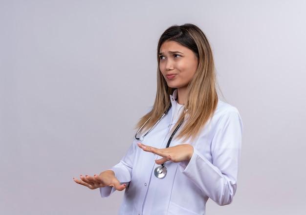 うんざりした表情で拒絶ジェスチャーで手のひらを上げる聴診器で白衣を着た若い美女医師 無料写真
