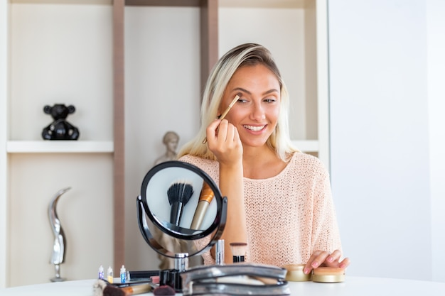 Young beautiful woman doing her make up near mirror Premium Photo