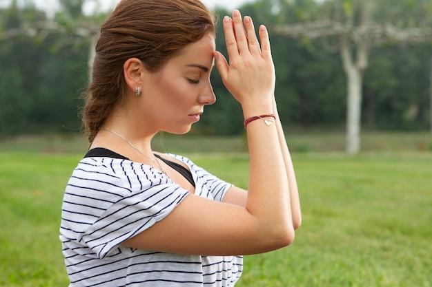 Giovane bella donna che fa esercizio di yoga nel parco verde Foto Gratuite