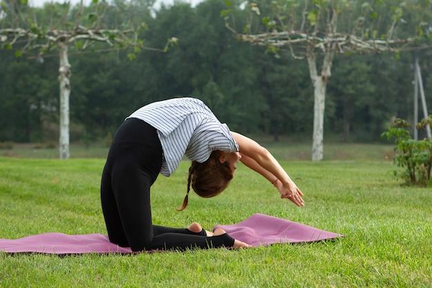 Молодая красивая женщина упражнения йоги в зеленом парке. концепция здорового образа жизни и фитнеса. Бесплатные Фотографии