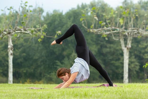 Молодая красивая женщина делает упражнения йоги в зеленом парке возле пруда Бесплатные Фотографии