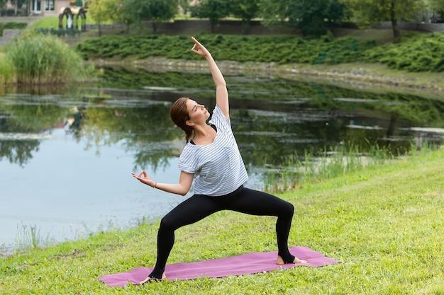 Молодая красивая женщина делает упражнения йоги в зеленом парке Бесплатные Фотографии