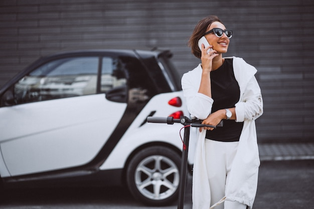 Young beautiful woman dressed in white riding scooter Free Photo