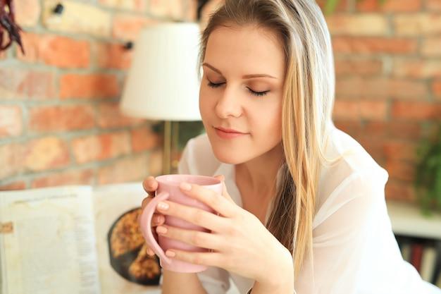 コーヒーやお茶を飲む若い美しい女性 無料写真