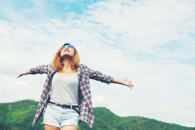 Young beautiful woman enjoying freedom and life in nature behind Free Photo