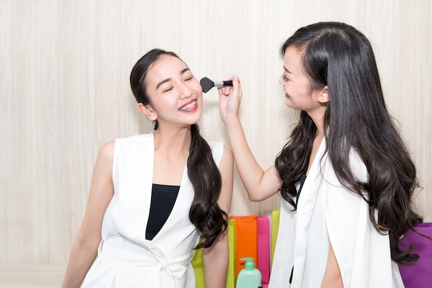 Young beautiful woman friendship test makeup with face for