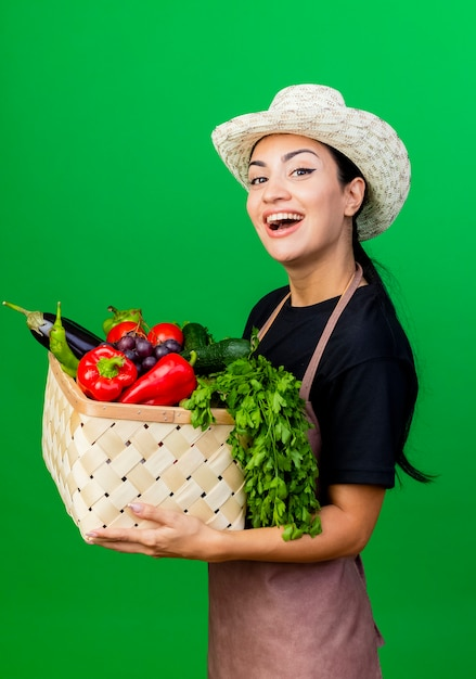 エプロンと帽子の若い美しい女性の庭師は幸せそうな顔で笑顔の野菜でいっぱいのバスケットを保持しています 無料写真