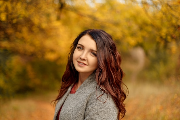 Young beautiful woman in grey coat sweather walking in autumn park with yellow and red leaves Premium Photo