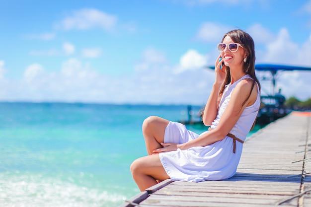 熱帯の海岸で楽しんで若い美しい女性。幸せな少女、カリブ海の島の海で青い空と青緑色の水 Premium写真