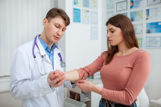 Молодая красивая женщина осматривает травмированную руку опытным врачом в больнице Premium Фотографии