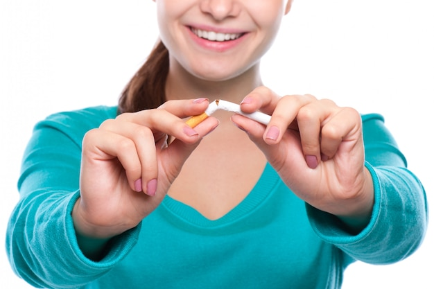 Young beautiful woman holding broken cigarette in front. Premium Photo