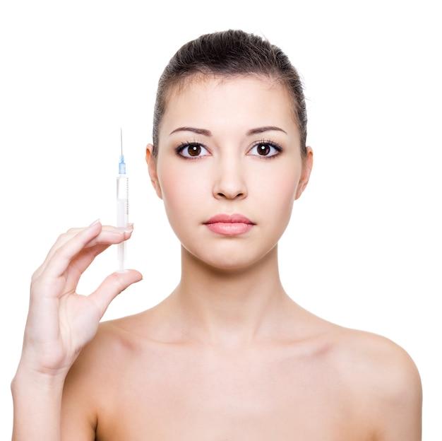 Молодая красивая женщина, держащая в руке медицинский шприц Бесплатные Фотографии