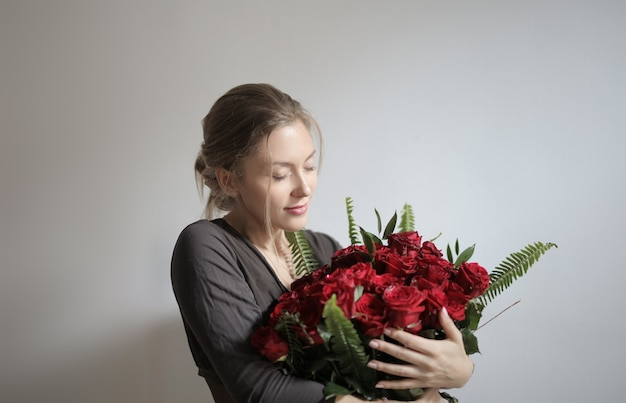 赤いバラを保持している若い美しい女性 無料写真