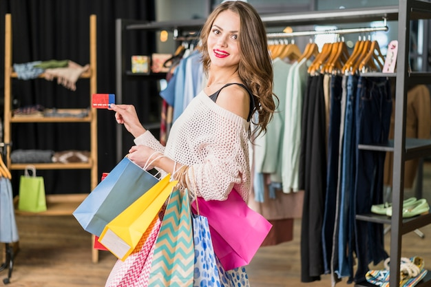 Young beautiful woman holding shopping bags and a credit card Free Photo