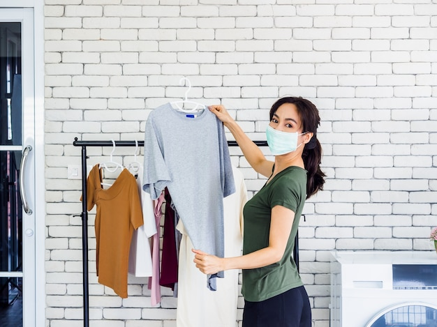 Young beautiful woman, housewife in casual wearing protective face mask hanging dry shirt with hanger on clothesline after washing near wash machine in laundry room on white wall. Premium Photo