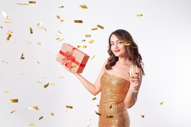 Молодая красивая женщина в золотом платье пьет шампанское, держа в руках красную подарочную коробку, веселится на вечеринке с золотым конфетти на белом фоне Premium Фотографии