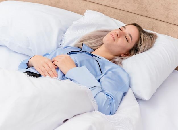 Молодая красивая женщина в синей пижаме, лежа на кровати, отдыхая на мягких подушках, мирно спит дома в интерьере спальни на светлом фоне Бесплатные Фотографии