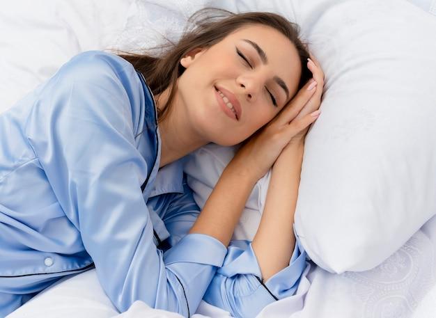 Молодая красивая женщина в синей пижаме, лежа на кровати Бесплатные Фотографии
