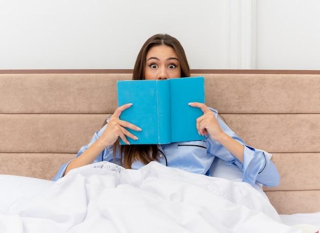 明るい背景の寝室のインテリアに驚いたカメラを見て本とベッドに座っている青いパジャマの若い美しい女性 無料写真