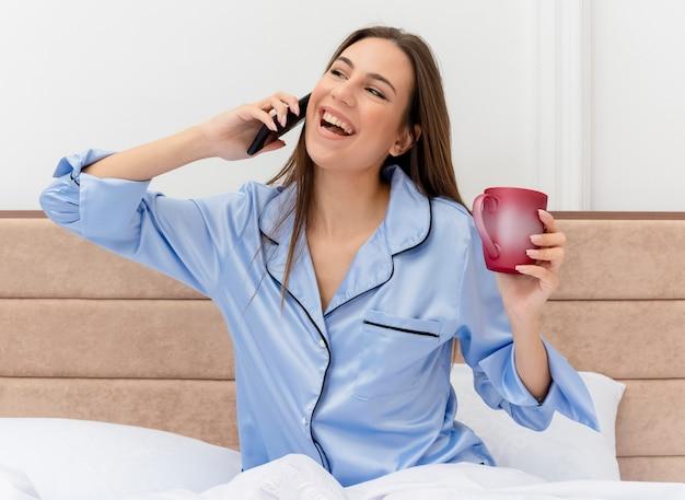 明るい背景の寝室のインテリアで携帯電話で幸せで興奮して話しているカメラを見てスマートフォンを保持しているコーヒーとベッドに座っている青いパジャマの若い美しい女性 無料写真
