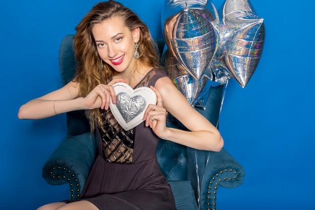Молодая красивая женщина в сером платье сидит на синем кресле с серебряным сердцем Бесплатные Фотографии