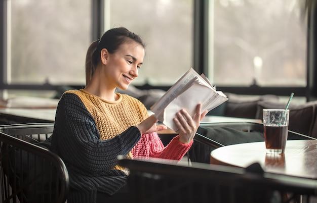 Молодая красивая женщина в оранжевом свитере читает интересную книгу в кафе Premium Фотографии