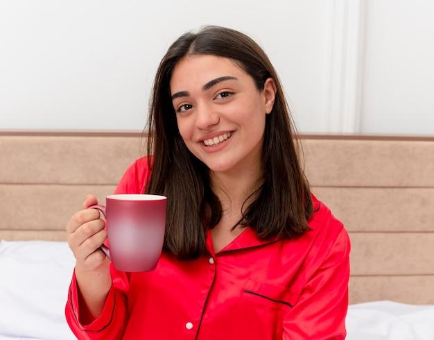 明るい背景の寝室のインテリアで元気に笑っているカメラを見てコーヒーのカップとベッドに座っている赤いパジャマの若い美しい女性 無料写真