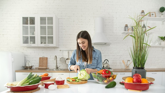 A young beautiful woman is preparing a salad of various vegetables in the kitchen. Free Photo