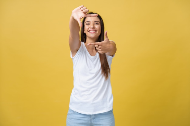 Young beautiful woman over isolated yellow background smiling making frame Premium Photo