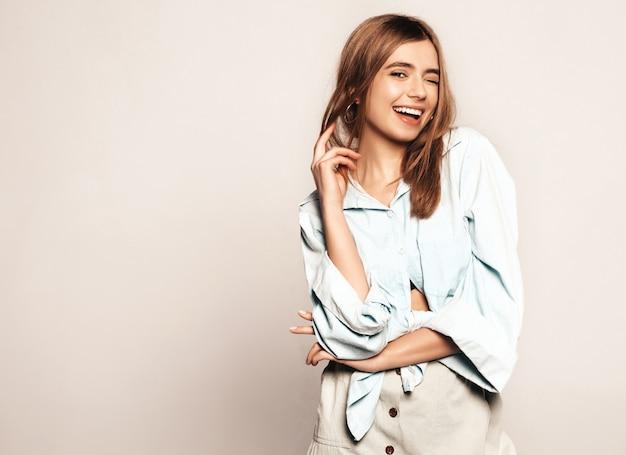 아름 다운 젊은 여자를 찾고. 캐주얼 여름 옷을 입고 유행 소녀입니다. 긍정적 인 재미있는 모델. 윙크 무료 사진