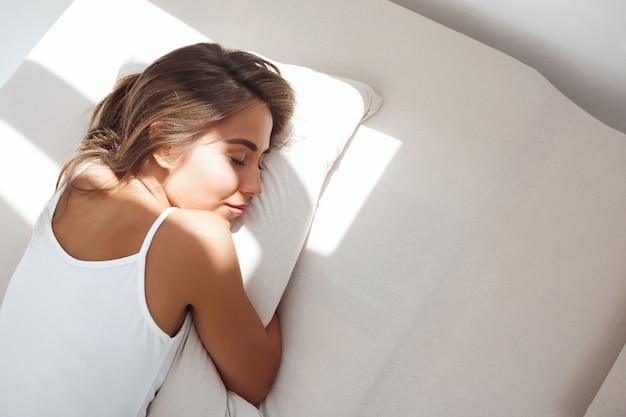 이른 아침에 침대에 누워 젊은 아름 다운 여자 무료 사진