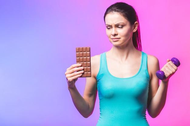 スポーツと不健康な食品の間で選択を行う若い美しい女性 Premium写真
