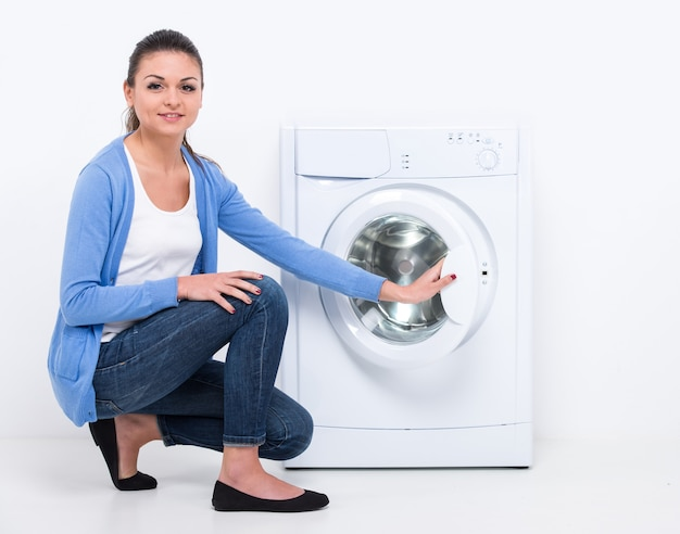 Young beautiful woman near the washing machine. Premium Photo