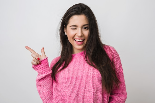 Young and beautiful woman in pink warm sweater, natural look, smiling, pointing finger aside, winking, portrait on , isolated, long hair, funny face expression, positive mood Free Photo