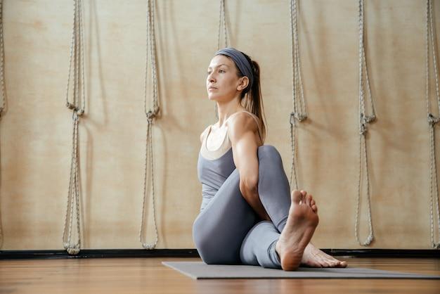 Молодая красивая женщина упражнениями йоги в студии йоги. гармония, баланс, медитация, релаксация, концепция здорового образа жизни Premium Фотографии