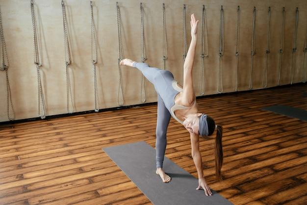Молодая красивая женщина упражнениями йоги в студии йоги. гармония, баланс, медитация, расслабление Premium Фотографии