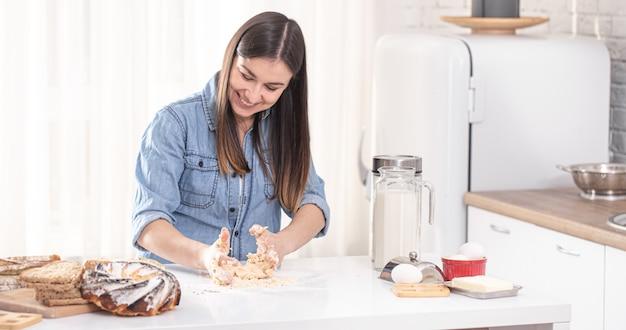 Молодая красивая женщина готовит домашнюю выпечку на кухне. Бесплатные Фотографии
