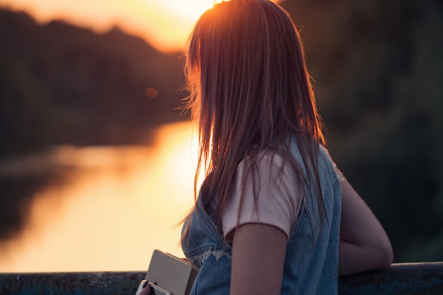 Young beautiful woman reading a book on the river bank during sunset Premium Photo