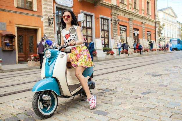 Young beautiful woman riding on motorbike city street Free Photo