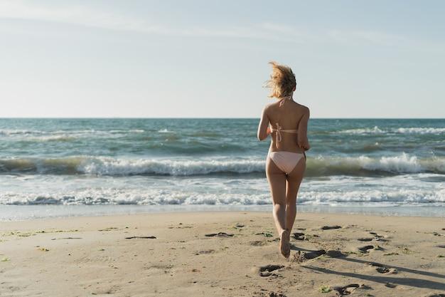 Young beautiful woman runs to the ocean Premium Photo