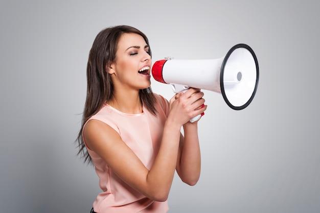 Молодая красивая женщина кричит в мегафон Бесплатные Фотографии