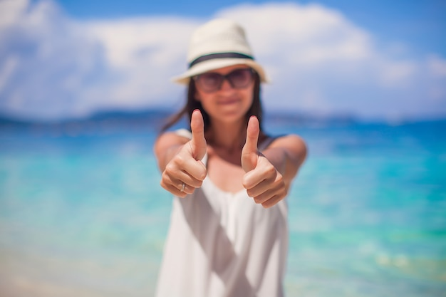 Young beautiful woman showing thumbs up on the beach Premium Photo