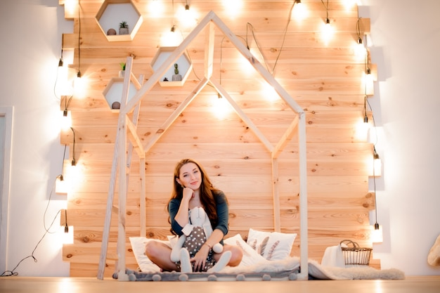 Young and beautiful woman sitting among lights of garland Premium Photo