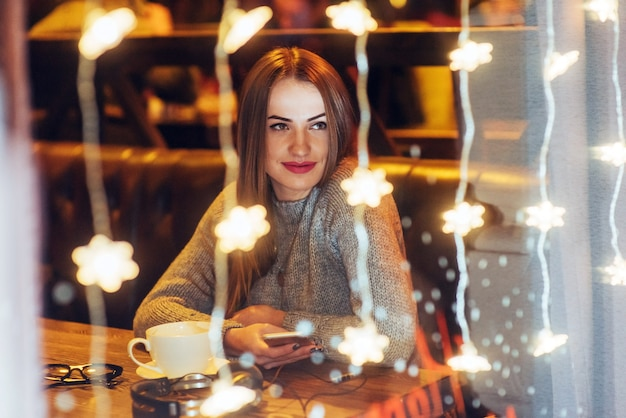 Young beautiful woman sitting in cafe, drinking coffee. christmas, new year, valentines day, winter holidays Premium Photo