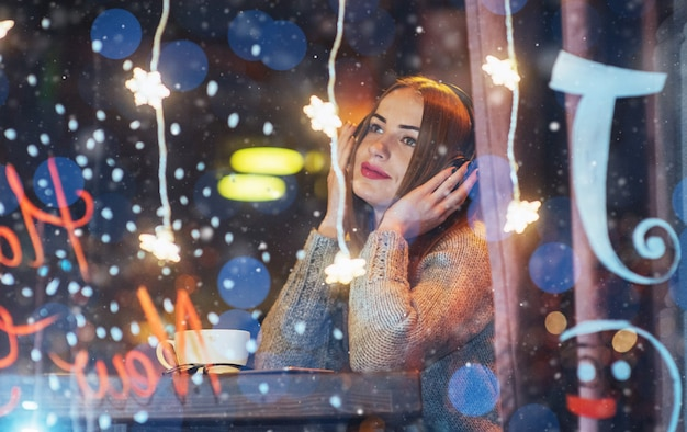 Young beautiful woman sitting in cafe, drinking coffee. model listening to music. christmas, happy new year, valentines day, winter holidays Premium Photo