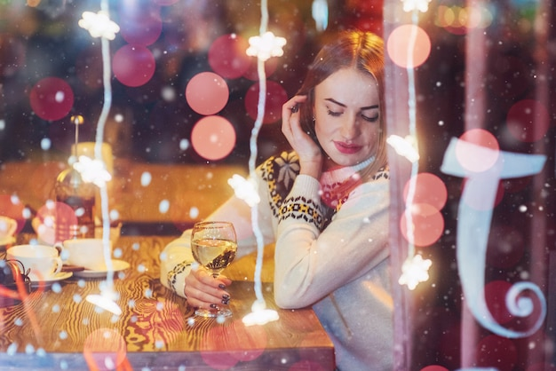 Young beautiful woman sitting in cafe, drinking wine. christmas, new year, valentines day, winter holidays Premium Photo