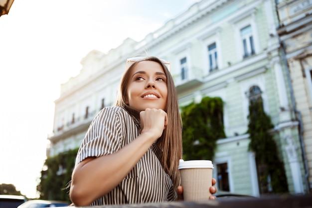 ベンチに座ってコーヒーを保持している若い美しい女性 無料写真