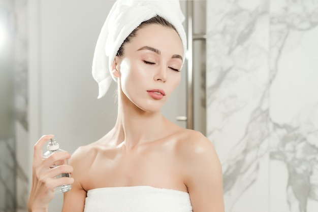 Young beautiful woman sprays perfume on her neck wrapped in towels in the bathroom.  beauty makeup and skin care concept Premium Photo
