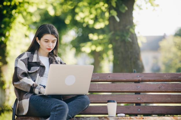 Молодая красивая женщина, стоя на скамейке, используя ноутбук Premium Фотографии